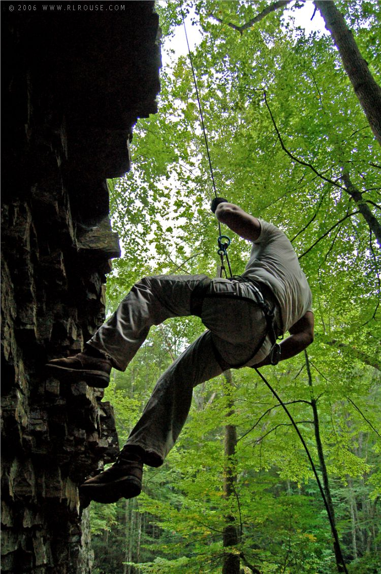 A mountaineer rappelling from the top of Backbone Rock.